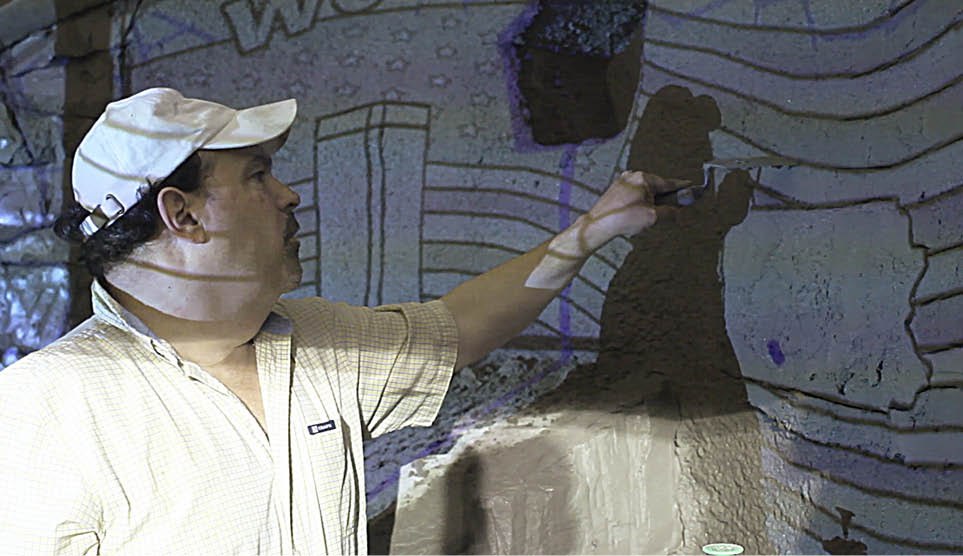 Seth Alexander pointing to a projected image on a concrete wall