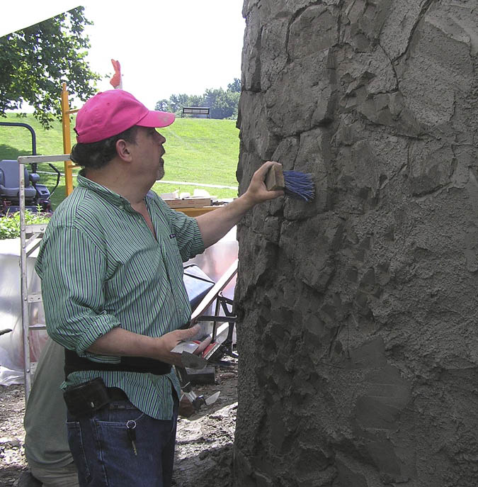 Seth R. Alexander touching a carved concrete wall.