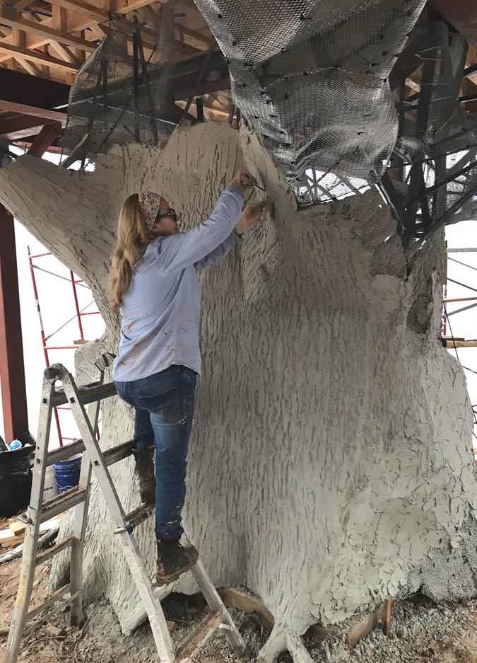 Eugenia Almeida sculpts the trunk of a tree out of concrete.