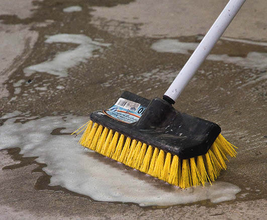 Cleaning concrete with a yellow brush.
