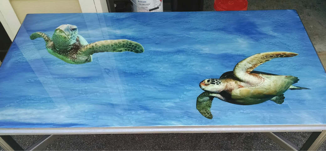 Detailed turtles on a blue concrete metallic epoxy coated table.