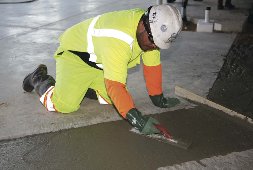 Anyone who works with concrete knows it can do a slow burn on exposed skin. That's why this well-protected worker has gloves, boots, a long-sleeved shirt and eye protection. The reflective gear and hardhat protect against unseen dangers.