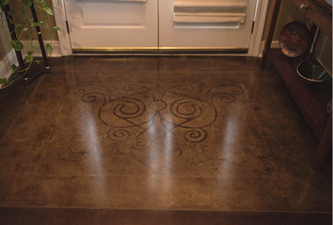 Stencil on a concrete in a dark brown on a orangish color floor finish.