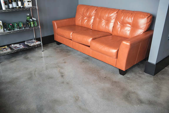 Concrete floor with a decorative look in grays and blacks contrasting an orange leather couch.