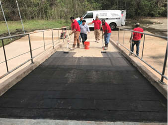 Workers transform concrete ramp.