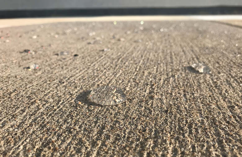 In blended water-based penetrating sealers, the silane penetrates deep into the concrete while the siloxane settles closer to the surface. This produces an appealing water-beading effect when the sealed surface gets wet.