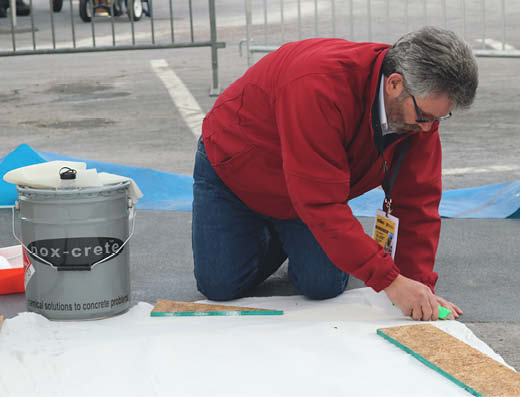 Marty O'Mara works on the concrete sealer application by Nox-Crete