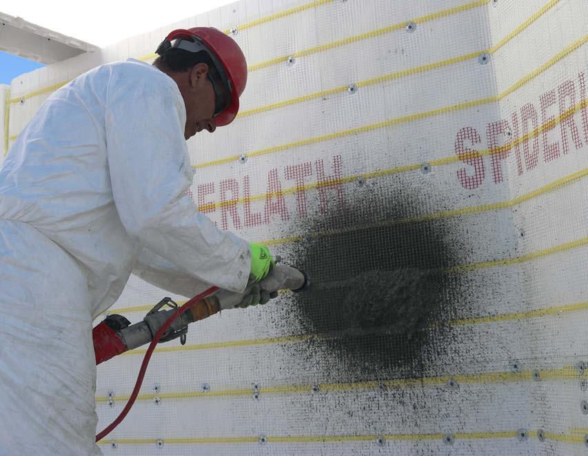 Danny applies scratch coat on wall covered with SpiderLath.