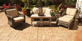 A nice patio set on a stamped concrete patio that has been stained a tan color.