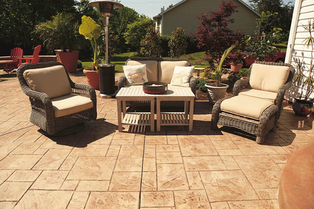 A stamped concrete patio with darker grout lines with patio furniture on it.