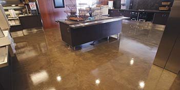 Concrete floor that has a very minimal design with stains and concrete countertops.