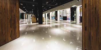 Shiny, white, polished concrete floor reflect the lights from above