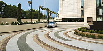 A large stained concrete driveway in front of a large hotel.