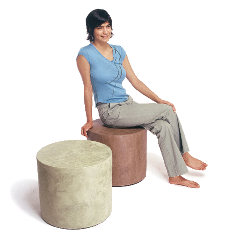 Two seats made out of glass aggregate and concrete and a woman with a blue shirt sitting on it.
