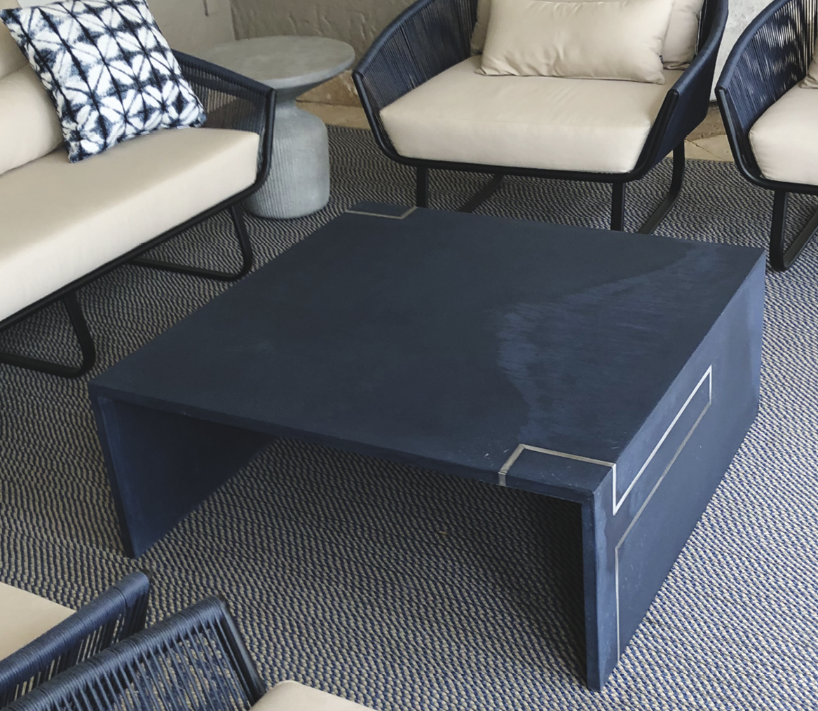 Concrete coffee table with infinity edge in black with gold accents.