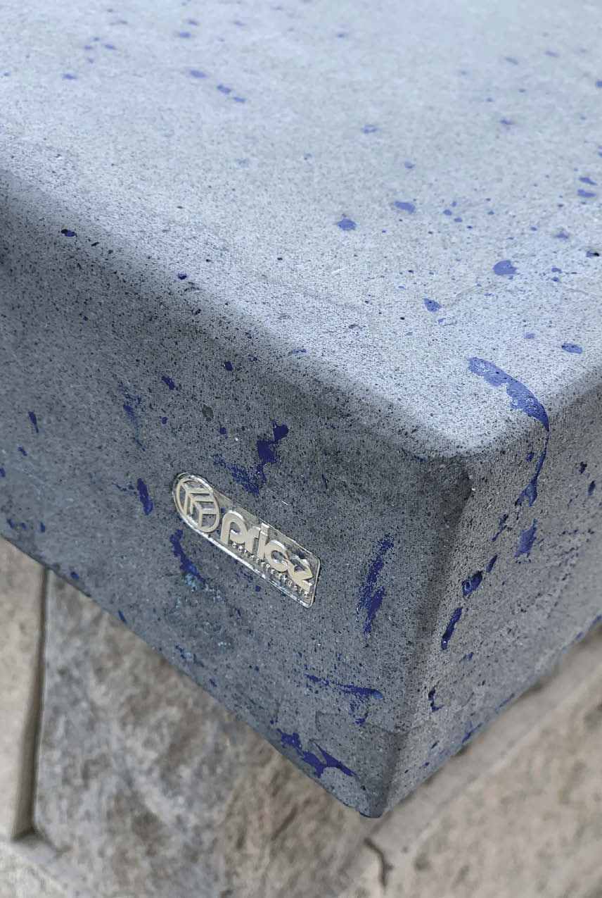 Gray concrete edge seeded with blue aggregate.