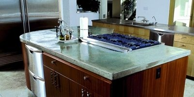 Large kitchen island with a green concrete countertop.