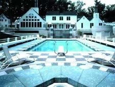 Black and white checkerboard concrete pool deck with diving board and large white house.