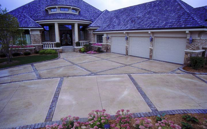 An oversized driveway is broken up with various squares creating dynamic visual effects.