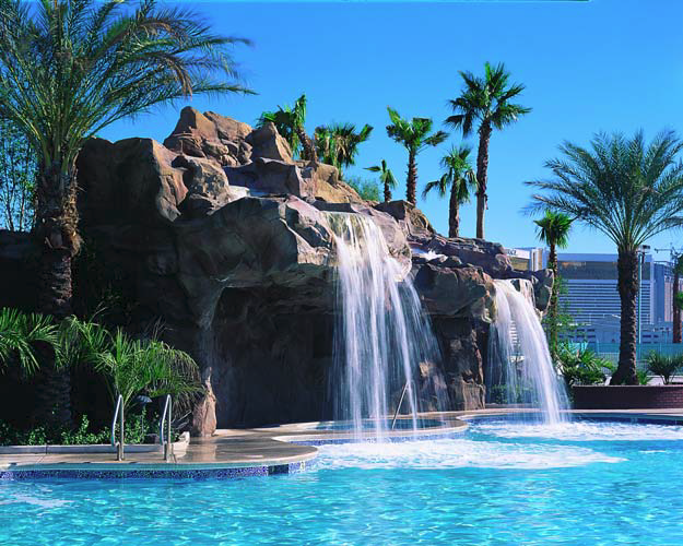 Large water features made of concrete that are found poolside make for an extravagant atmosphere.
