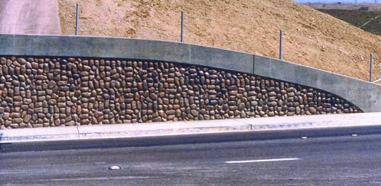Decorative concrete along the side of a highway brings color and texture to an otherwise boring hillside.
