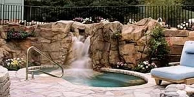 Custom faux rock water feature takes this pool scene to the next level.