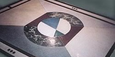 Terrazzo is used to create a BMW logo on this concrete floor.