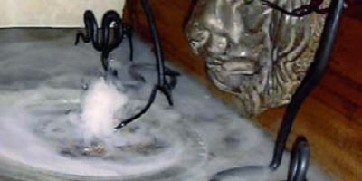Concrete countertop burping dry ice steam in front of a concrete lion head.