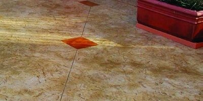 Red stained concrete diamond shapes blend with the control joint that runs through the middle of the concrete slab.