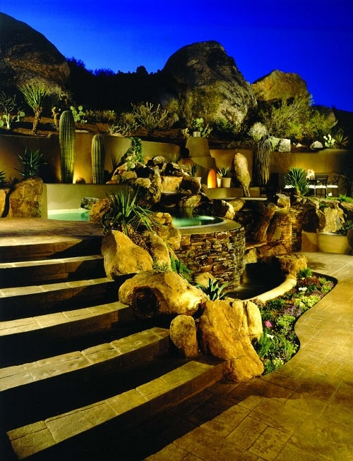 Boulders line a stamped concrete patio and stamped concrete stair treds near a misty spa on an Arizona hillside.