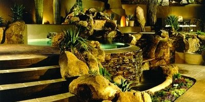 Misty hillside spa surrounded by amazing concrete rocks tumbling down beside stamped concrete stairs.