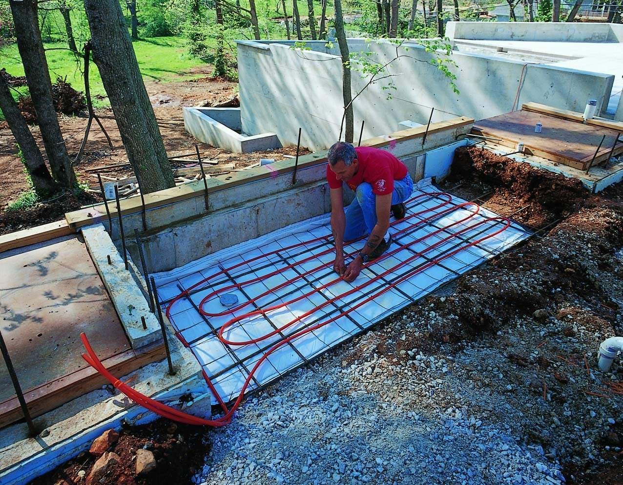Radiant floor heating tube being placed above the rebar before the concrete is poured.