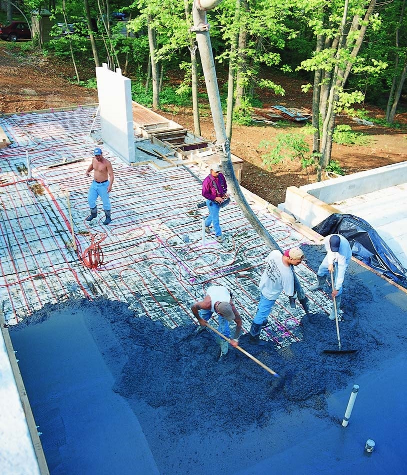 Team of concrete contractors spreading integral colored concrete over a floor with radiant heating tubes installed.