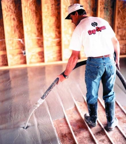 Concrete contractor pouring thin set cementious topping onto a floor with hydronic radiant heating tubes.