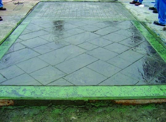 Dark green and light green stamped concrete slab with a green splotchy border showing pigmented color release after stamping a concrete slab.