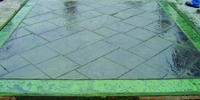 Environmentally friendly stamped concrete pigmented color release has been used on the multicolored green concrete slab in a slate look.