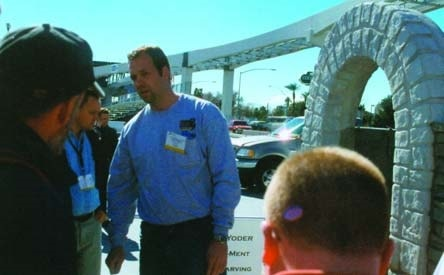 Man talks with attendees at World of Concrete 2003 about his carved concrete archway.