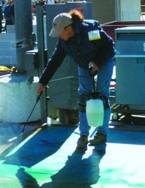 A women spraying concrete acid stain in a sea blue onto a concrete slab at the World of Concrete 2003