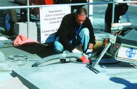 Tom Graf of Graf Concrete polishes a concrete pad at the World of Concrete 2003 with an HTC machine and vacuum.
