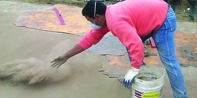 Concrete contractor throwing color hardener on a fresh concrete slab ready to be stamped or textured.