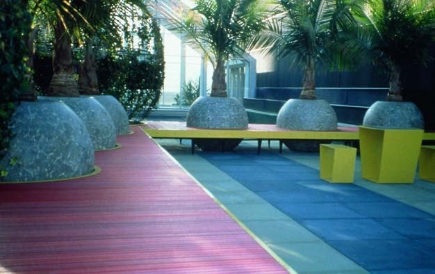 Colorful overlay surface with round, ball shaped planters for the palm trees.
