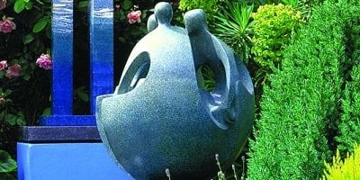 A concrete sculpture in a garden of what looks like people morphing into a sphere with heads facing each other.
