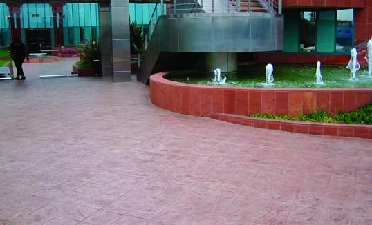 Brick red concrete overlay near a fountain with a red retaining wall.