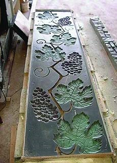 Concrete form liner of grapes and grape leaves on a vine. when used in a concrete form, the grapes will leave an image of the vine on the concrete.