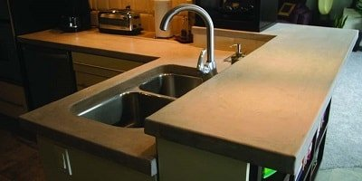 Concrete kitchen countertop has a bi level bar area and is an L shaped kitchen.
