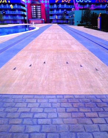 "Bowling Pin Pool area at Pop Century Resort features concrete ""wood planks."""