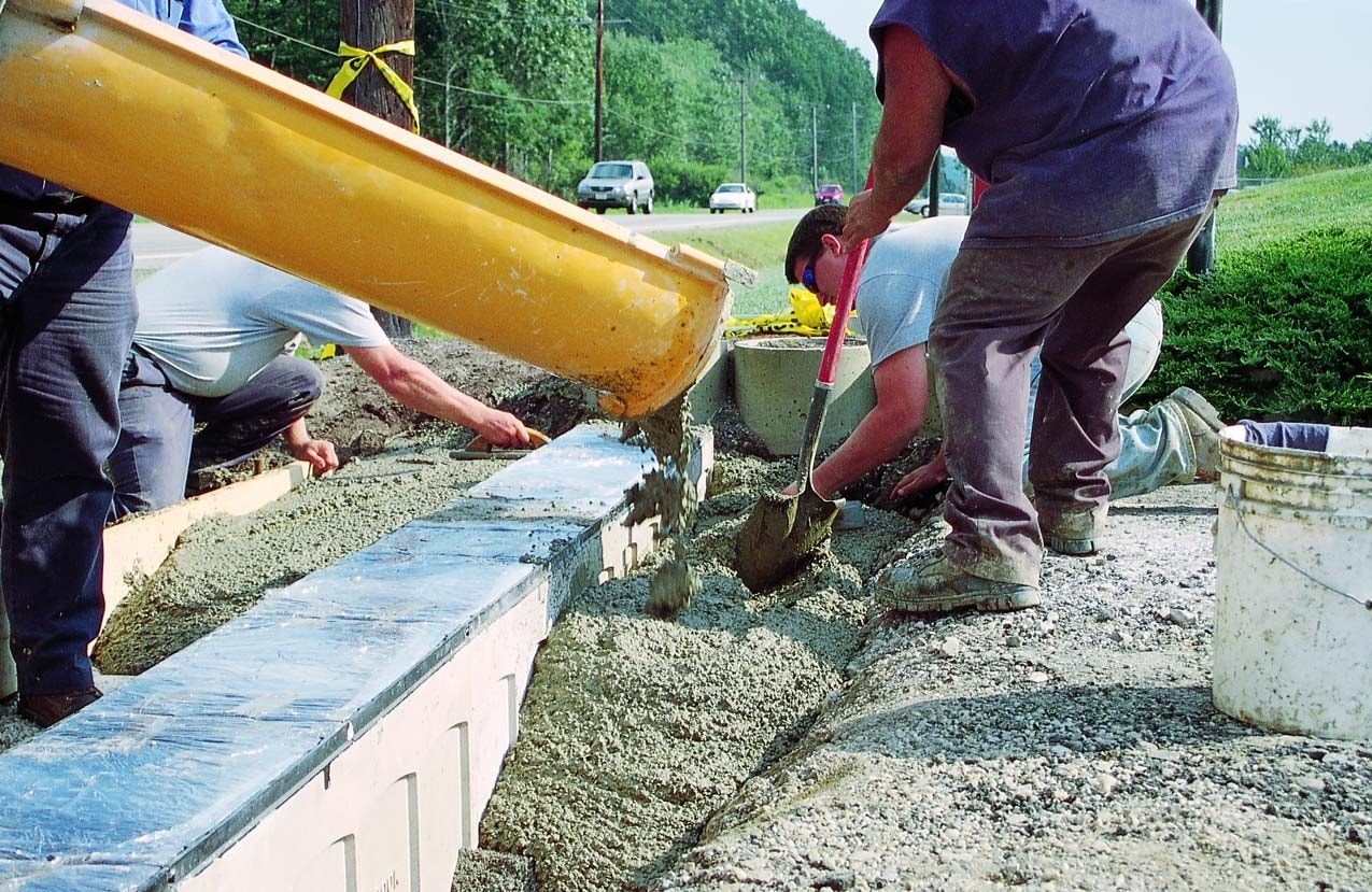 Concrete being placed within a form and around a decorative concrete form.