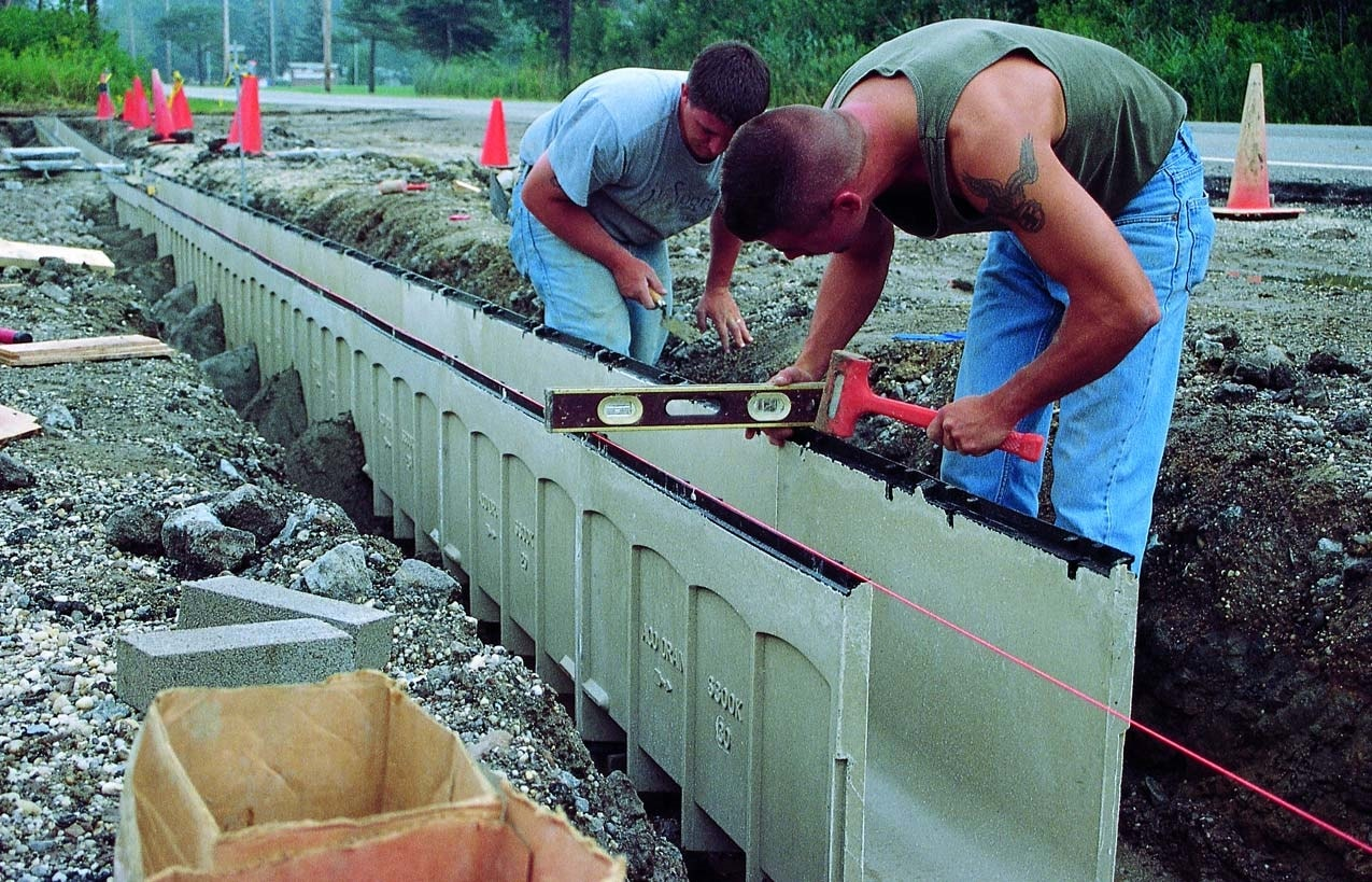 Leveling and installing a drain prior to pouring concrete into a form.