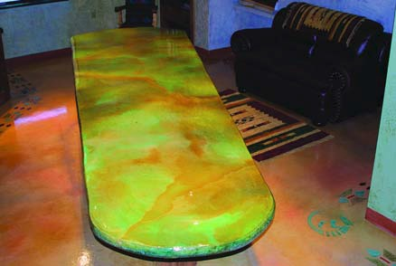 A striking concrete countertop stained with green and orange hues.