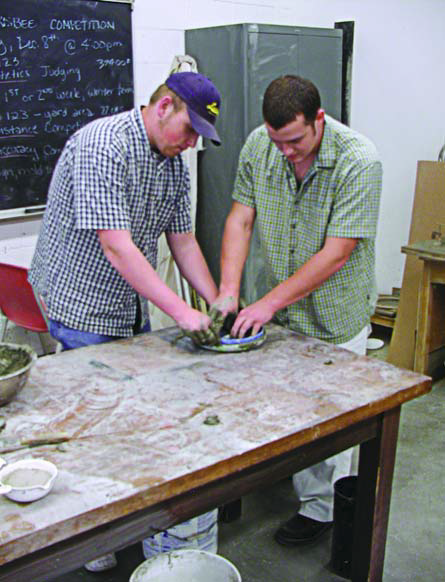 Two students working diligently to make the best, longest flying concrete frisbee,